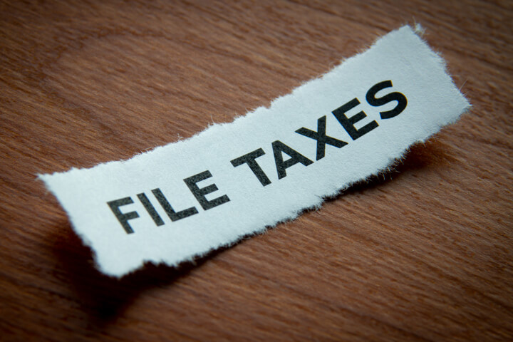 Torn piece of paper with the text File Taxes printed on it with vignette on wood background