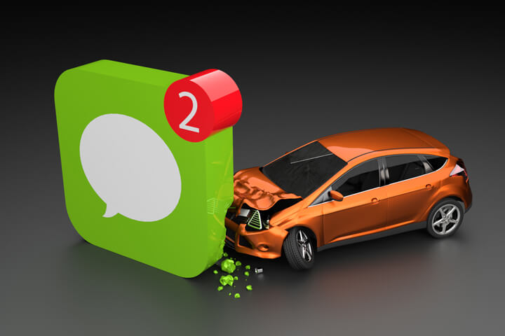 Orange compact car crashed into corner of cell phone message app icon texting while driving concept on dark background