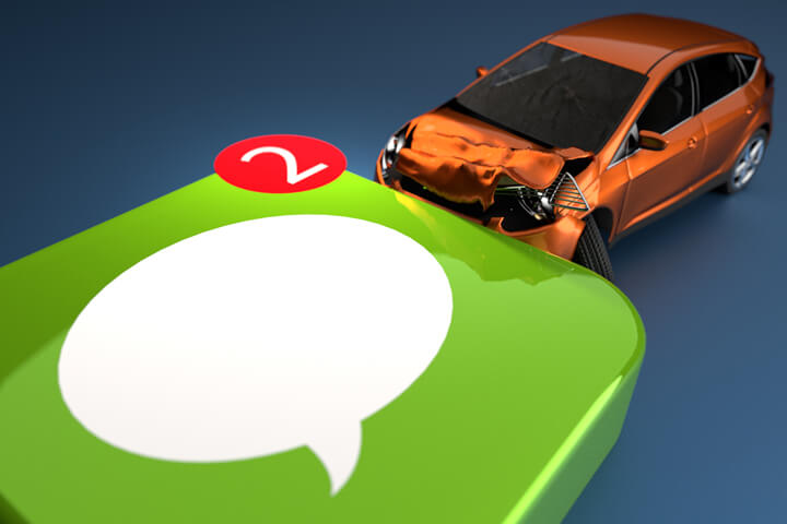 Concept image for texting while driving showing small car crashed into side of reflective messaging app icon