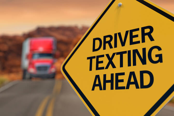 Yellow road sign reading Driver Texting Ahead with oncoming semi truck in blurred in background
