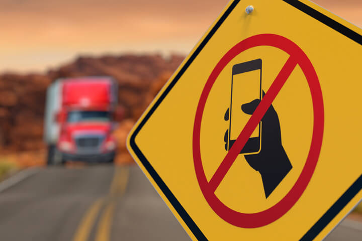 Road sign with icon of hand holding cell phone crossed out concept for no texting while driving