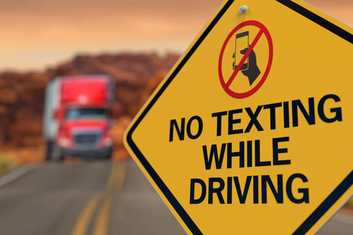 Yellow road sign reading No Texting While Driving with no texting icon and oncoming semi truck in background