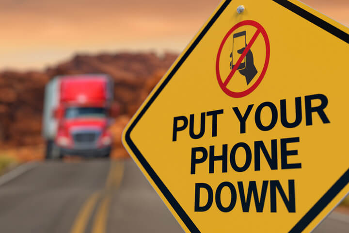 Road sign with Put Your Phone Down and no texting icon with oncoming semi truck on highway in background