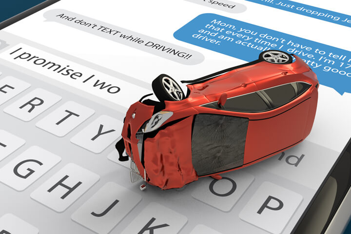 Red car with rollover accident damage lying on cell phone screen with message app and keyboard open