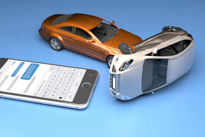 Texting while driving concept image showing two cars crashed next to iphone with messaging app on screen